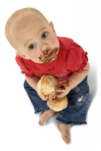 Baby with face covered in chocolate.  Clipping path.  Full body over white.